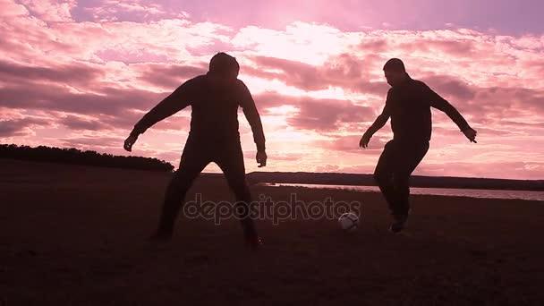 Sonnenuntergang und Silhouetten der Männer spielen Fußball, kick einen Fußball, Torwart fängt ball