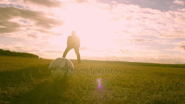 Beautiful sunset and silhouettes of men playing football, kick a soccer ball, goalkeeper catches ball.