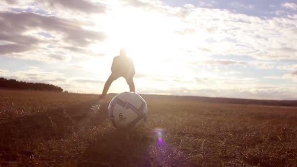 Krásný západ slunce a siluety mužů hrajících fotbal, kick fotbalový míč, brankář chytí míč.