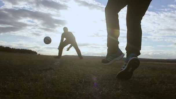 Gyönyörű naplemente és sziluettek a férfiak futballozni, rúgni egy futball-labda, a kapus fogások labda.