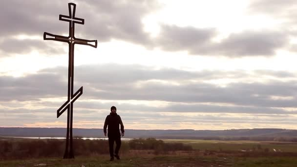 Silhouette man on top of the mountain looking with hope at the Christian Cross. A man making a confession to the cross, background sunset.