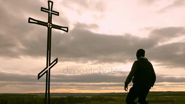 Silueta muže na vrcholu hory, hledí s nadějí na křesťanské kříže. Člověk přiznání na kříž, na pozadí západ slunce.
