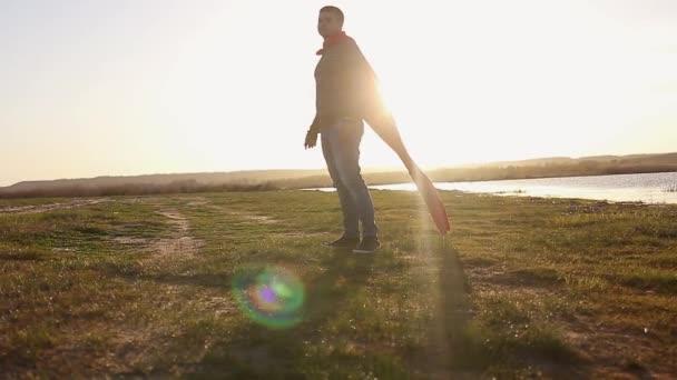 Luomo gioca supereroe sul fondo del cielo al tramonto. Sagoma di un uomo a immagine di un superuomo, bellissimo tramonto. Il concetto di potenza delleroe alla ricerca del sole