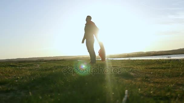 Ember játszik szuperhős napnyugtakor ég háttér. A képen egy felsőbbrendű ember sziluettje gyönyörű naplemente. A hős a nap látszó hatalom fogalmának.