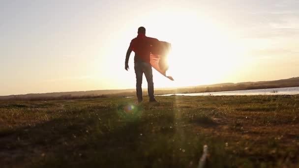 Luomo gioca supereroe sul fondo del cielo al tramonto. Sagoma di un uomo a immagine di un superuomo, bellissimo tramonto. Il concetto di potenza delleroe alla ricerca del sole.