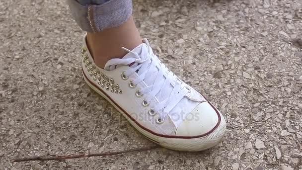 Bílé tenisky na nohách dívka na pozadí asfalt