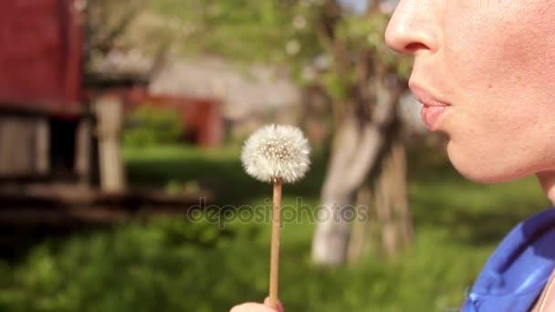 Happy krásná žena fouká Pampeliška na zahradě. Roztomilá dívka si hraje s blowball