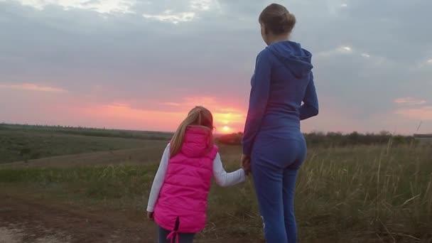 Matka a dcera šťastný v lásce při západu slunce. Ke dni matek. Šťastná rodina.