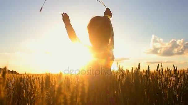 Malá holčička k vlně ruce na louku s západ slunce. Happy hezká dívka v poli při západu slunce.