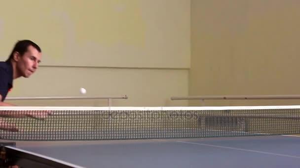 Young Sport férfi asztalitenisz játékos a játék a régi tornaterem. Akció lövés.