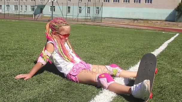 Hezká mladá dívka, ošumělý, se nachází na zeleném trávníku na stadionu. Odpočinku od skateboardingu. Koncept venkovních aktivit