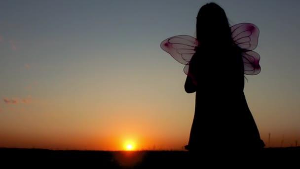 Silhouette eines glücklichen kleinen Mädchens in einem Feenkostüm mit Flügeln. das Kind präsentiert sich als Zauberin, das Konzept des Spielens und der Fantasie der Kinder.