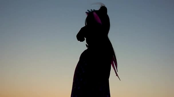 Sziluettjét boldog kis lány öltözött szárnyakkal tündér jelmez. A gyermek mutatja be magát, mint egy boszorkány, a koncepció a gyermek játék és a képzelet.