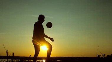 Mladý muž hraje s míčem na pláži s krásným západem slunce pozadím. Silueta muže hrát míč ve vzduchu s západ slunce, východ slunce dětství, vyrovnanost, sport, životní styl koncept