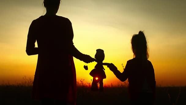 Silueta máma a dcera při západu slunce, drží hračka panenka a hledí do dálky. Silueta dívka hraje s panenkami