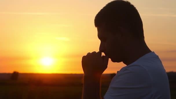 Silhouette eines Mannes, der bei Sonnenuntergang betet. Silhouette Mann Nahaufnahme beten mit Sonnenuntergang Hintergrund.