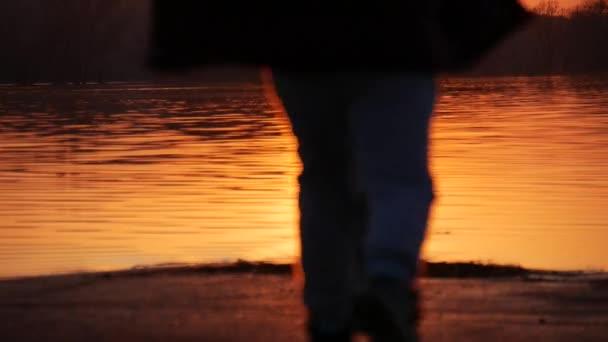 I bambini giocano su un lago al tramonto. Siluette di una piccola ragazza e ragazzo trascorrere del tempo insieme successivamente, correre e giocare. Il concetto di amicizia dei bambini, riprese in slow motion