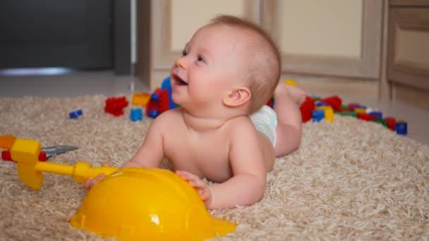 Dítě hraje s barevné bloky konstruktoru na podlaze u dětí pokoj