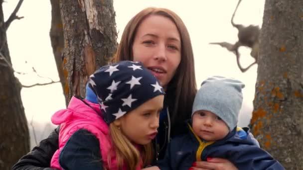 Mladá matka a její děti venku na krásný jarní den. Matka a dvě děti si hrají v parku. Rodinnou zábavu na pozadí nádherné přírody. Aktivní rodinná dovolená v přírodě