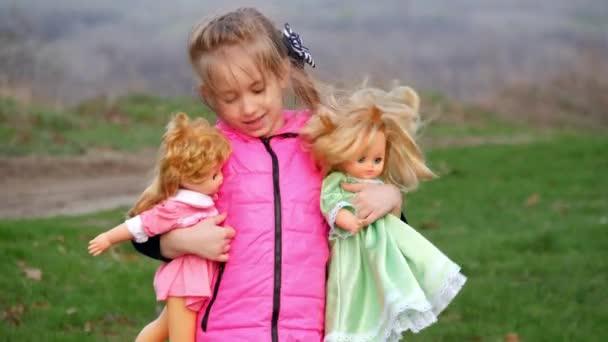 Mladá dívka si hraje s panenkami na venku