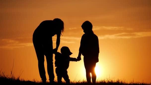Matka a dvě děti siluety při západu slunce. Koncept přátelské rodiny.