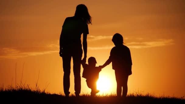 Anya és két gyerek sziluettek a naplemente. A barátságos családi fogalmát.