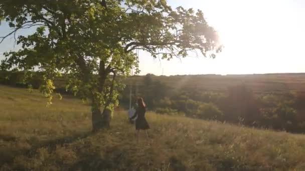 Glückliche junge Mutter und kleine Tochter auf einer Schaukel bei Sonnenlicht. Hübsches Mädchen, das auf einer Holzschaukel sitzt und den goldenen Sonnenuntergang betrachtet. Glückliches Familienkonzept.