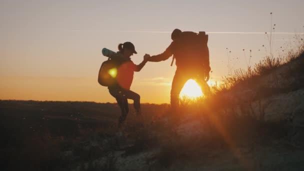 Silueta týmu na vrcholu hory. Sport a aktivní život lidí s mužem a dívkou. Týmovová práce pár asistenčních mužů a žen, pomoc na vrcholku hory.