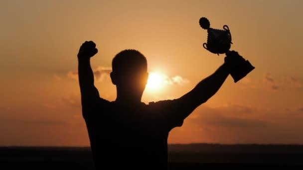 Sziluettjét legjobb ember díj győztes győzelem trófea szakmai bajnok Challenge, holding kupa trófeát alatt a fej a siker a cél. Fogalom, mint a győzelem, a siker és a sport a bajnok.