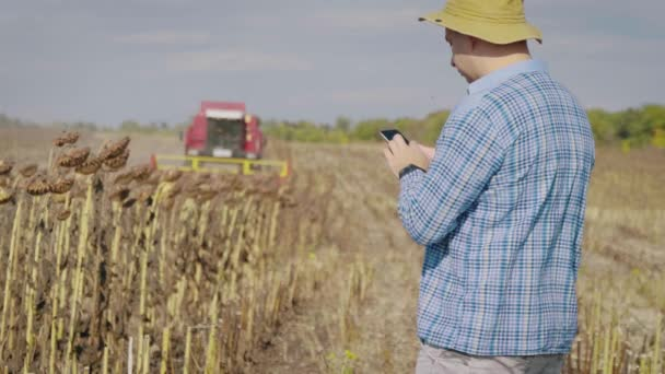 Handsome farmer with smartphone standing in field sunflower with combine harvester in background. Concept modern technology application in agricultural growing activity.