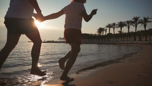 Silhouette of the father and his little daughter are running happily into the sea at sunset. Splashes fly into their faces. Happy family with a child on vacation at the beach.