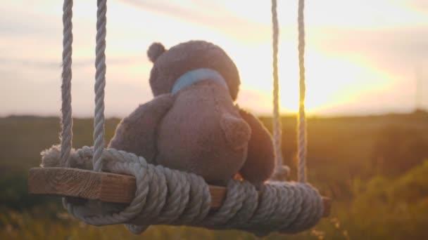 Teddy medvěd sedí při západu slunce na houpačce. Pojetí osamění.