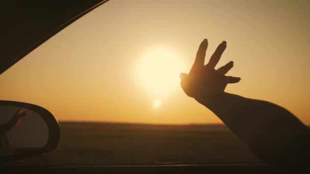 Girl looks at the sun through her hand at sunset.