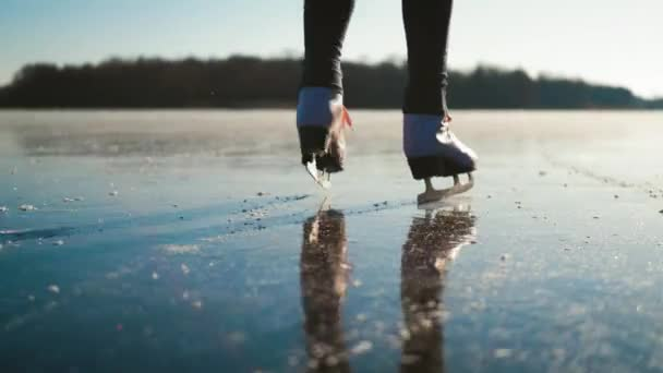 Young woman ice skating on a frozen lake on a freezing winter day. Legs of skater on winter ice rink in outdoors. People, winter sport and leisure concept.