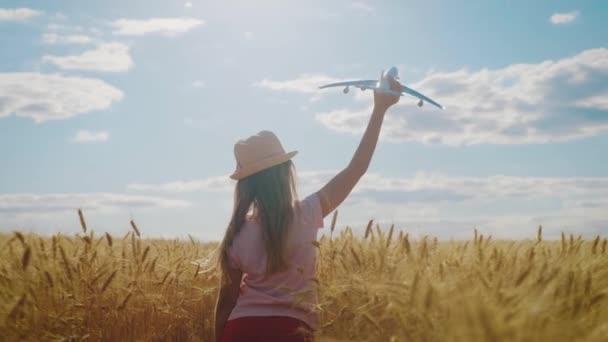 Aranyos lány játszik játék repülőgép a búzamezőn naplementekor. Silhouette a gyermek játszik játék repülőgép a szabadban. Koncepció utazás és szabadság.