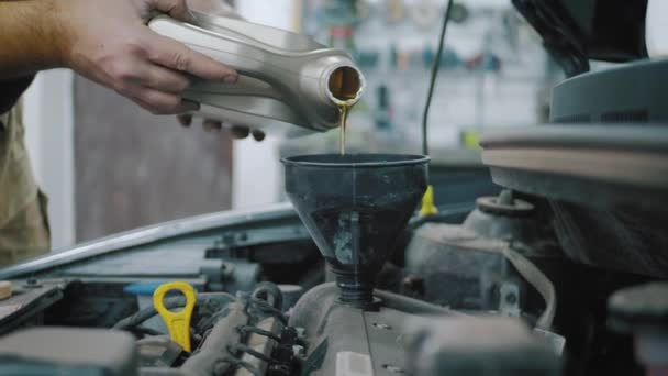 Údržba vozu servisní mechanik nalití nové mazivo olej do motoru auta. Proudí čerstvý nový čistý syntetický olej do motoru auta. Vyměňte motorový olej v autě.