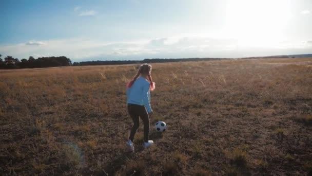 Holka si hraje s fotbalovým míčkem. Malá holka kope fotbal. Dětský sen stát se fotbalistou.