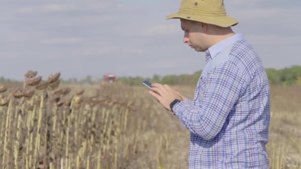 Pohledný farmář s chytrým telefonem stojící na poli slunečnice s kombajnem v pozadí. Koncepce moderní technologie v zemědělské pěstitelské činnosti.