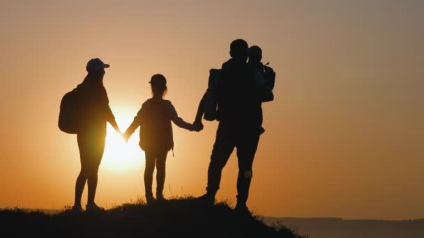 Silhouettes of father, mother and children hiking. Baby sits on the shoulders of his father. Hiking backpackers trekking mountains summer. Young family on travel adventure vacation.
