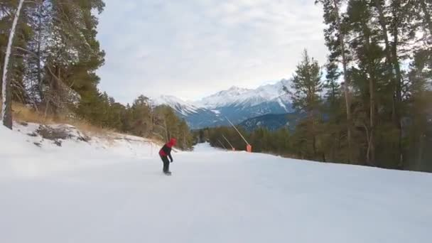 Snowboarder auf Snowboard läuft die Piste im Skigebiet hinunter. Wintersport und Erholung, Freizeitaktivitäten im Freien.