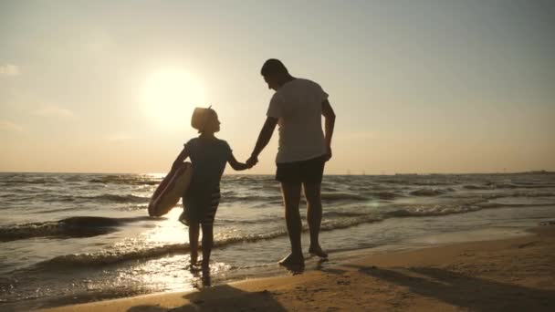 Silhouettes father and daughter play on the beach at sunset. Concept of friendly family, travel, lifestyle.