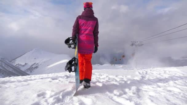 Dívka se snowboardem sedí na vrcholu a těší horské krajiny. Sportovní žena ve zasněžených horách. Krásný úžasný den zimní hory.