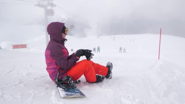 Mädchen mit Snowboard sitzt oben und genießt die Berglandschaft. Sportlerin in verschneiten Bergen. wunderschöner Tag Winter Berge.