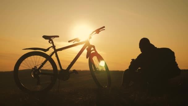 Silueta horského cyklisty na kopci s kolem při západu slunce. Sport, cestování a aktivní životní koncept.
