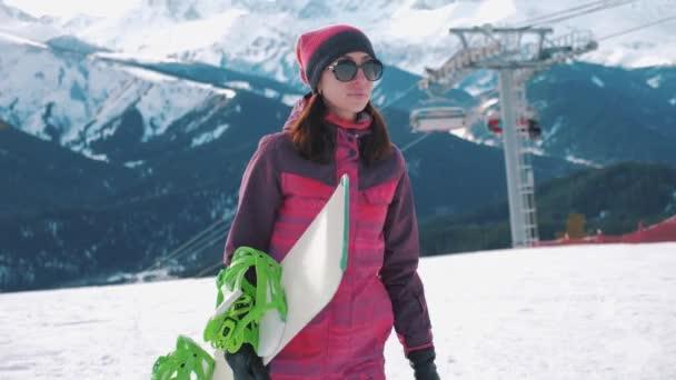 Snowboarderin mit Snowboard in der Hand im Skigebiet. Sportlerin in verschneiten Bergen. sonniger Wintertag im Skigebiet.
