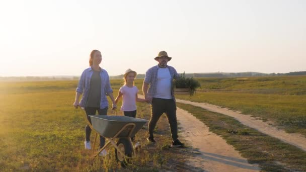 Mladá rodina se baví venku na farmě. Zahradnice při západu slunce tlačila na kolečka se zeleninou. Rodina pracuje na venkově. Při západu slunce se tu nacházejí siluety. Šťastný rodinný koncept.