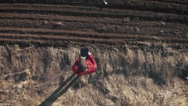 Aerial view of woman farmer with digital tablet computer looks at a fresh plowed field after winter, she makes plans for harvesting and preparing for sowing.