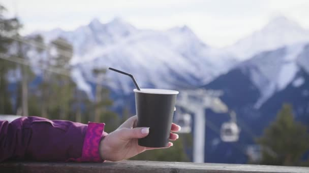 Woman drinking warm tea in the rustic wooden terrace on mountain. Girl is enjoying the panoramic view of snowy peaks. Happiness and serenity concept.