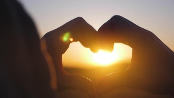Fiatal gyönyörű lány teszi szív a kezét a szív alakú keretezés lenyugvó nap a naplementét. Boldog exkluzív életmód pillanat, megosztása időt, pihentető érzelmi koncepció.
