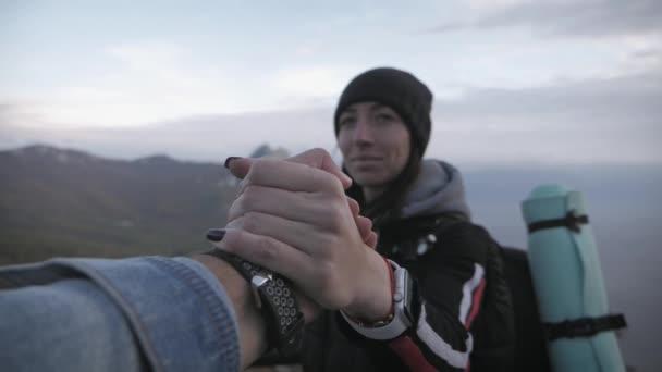 Turista pomáhá přítelkyni při trekingu na kopci. Horolezec pomáhal kolegovi lézt, muž s batohem natáhl k příteli pomocnou ruku. Koncept týmové práce.